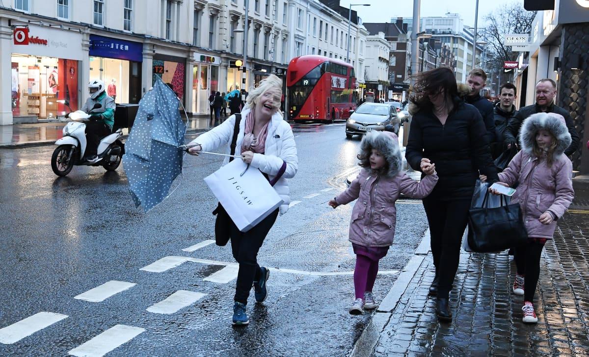Kadulla käveleviä ihmisiä. Naisen sateenvarjo on kääntynyt ympäri.