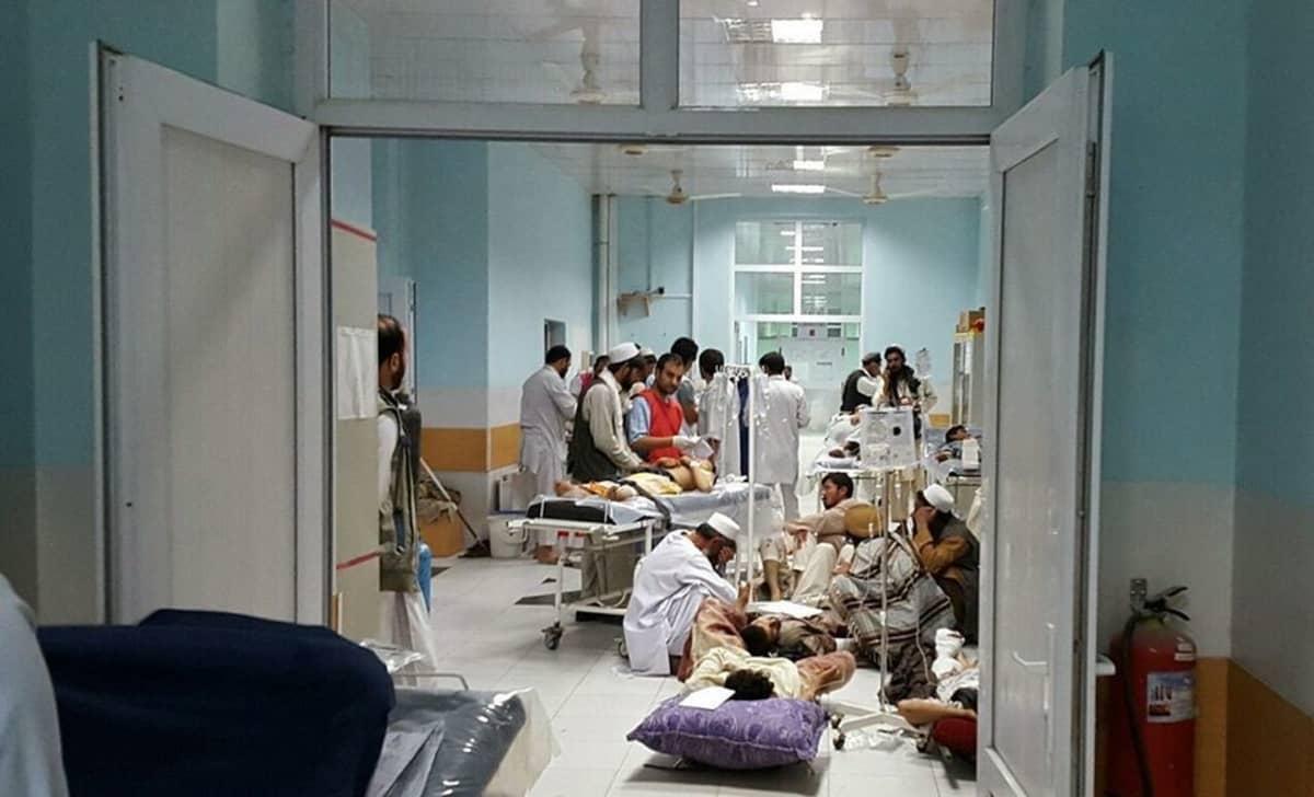 Sairaalahuone ja osa käytävää. Ihmisiä hoidetaan paareilla ja lattialla.