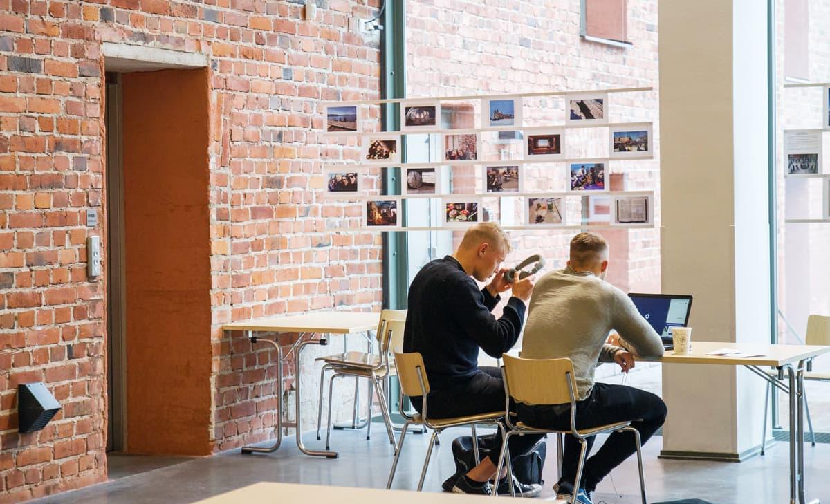kaksi miestä opiskelemassa koulun aulassa