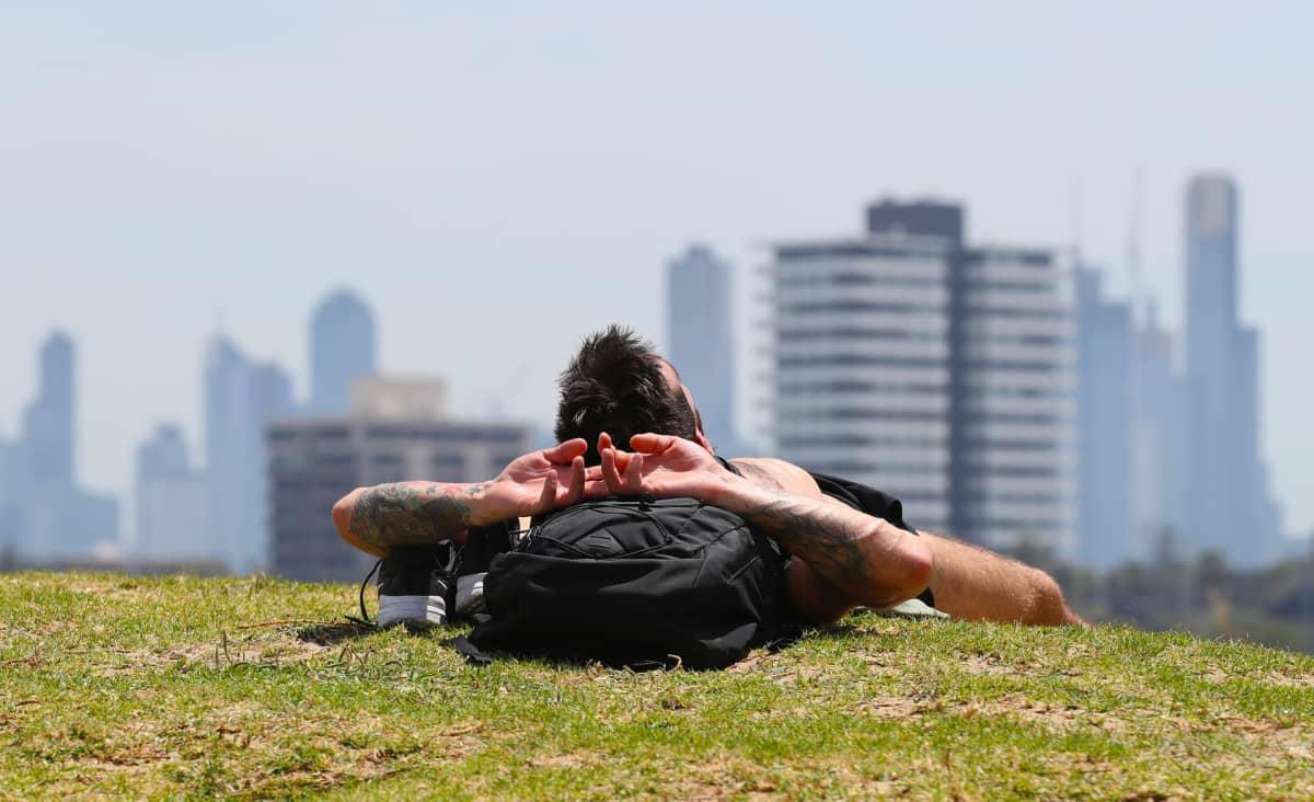 Mies ottaa aurinkoa Melbournessa.