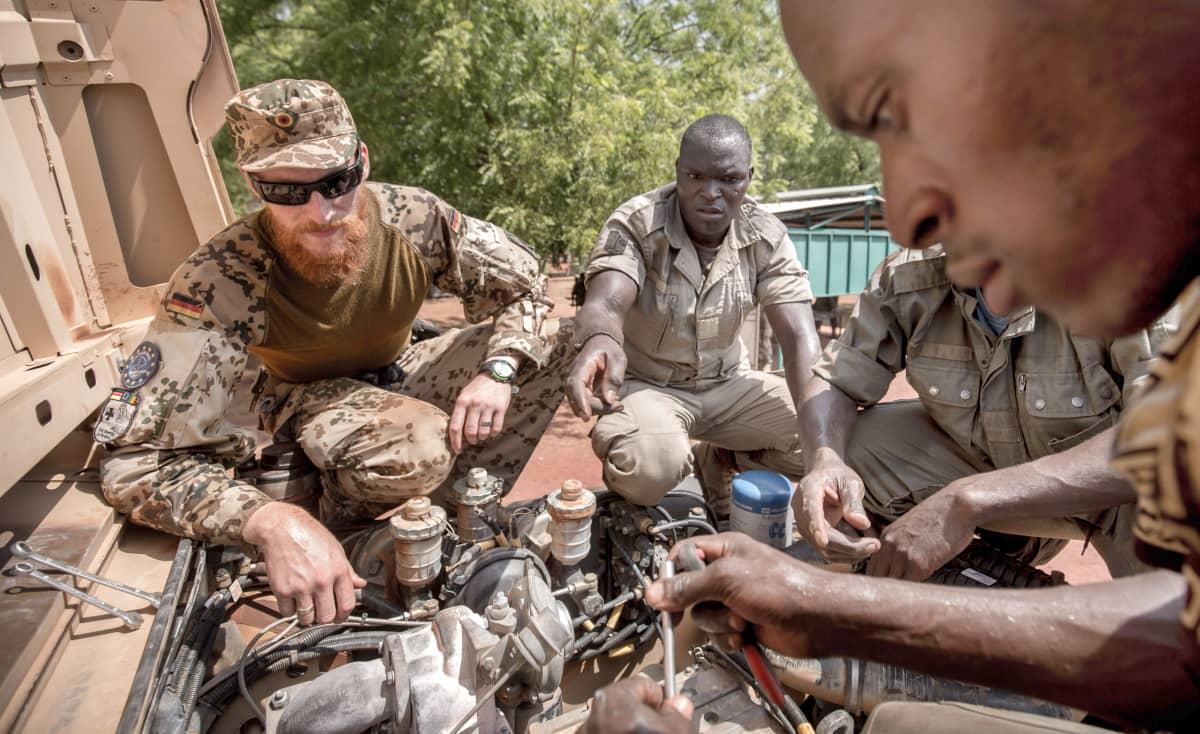 Malilaiset sotilaat korjaavat kuorma-auton moottoria harjoitusleirillä.