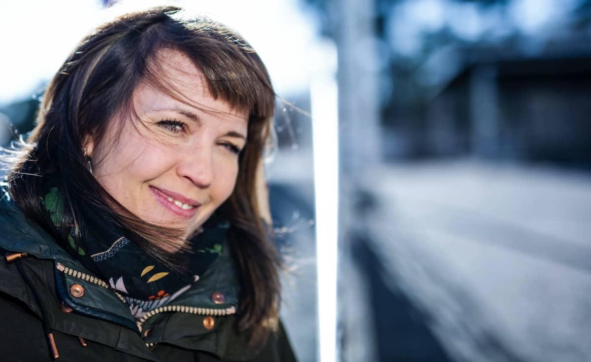 Julia Korkman hymyilee ulkona tuulessa