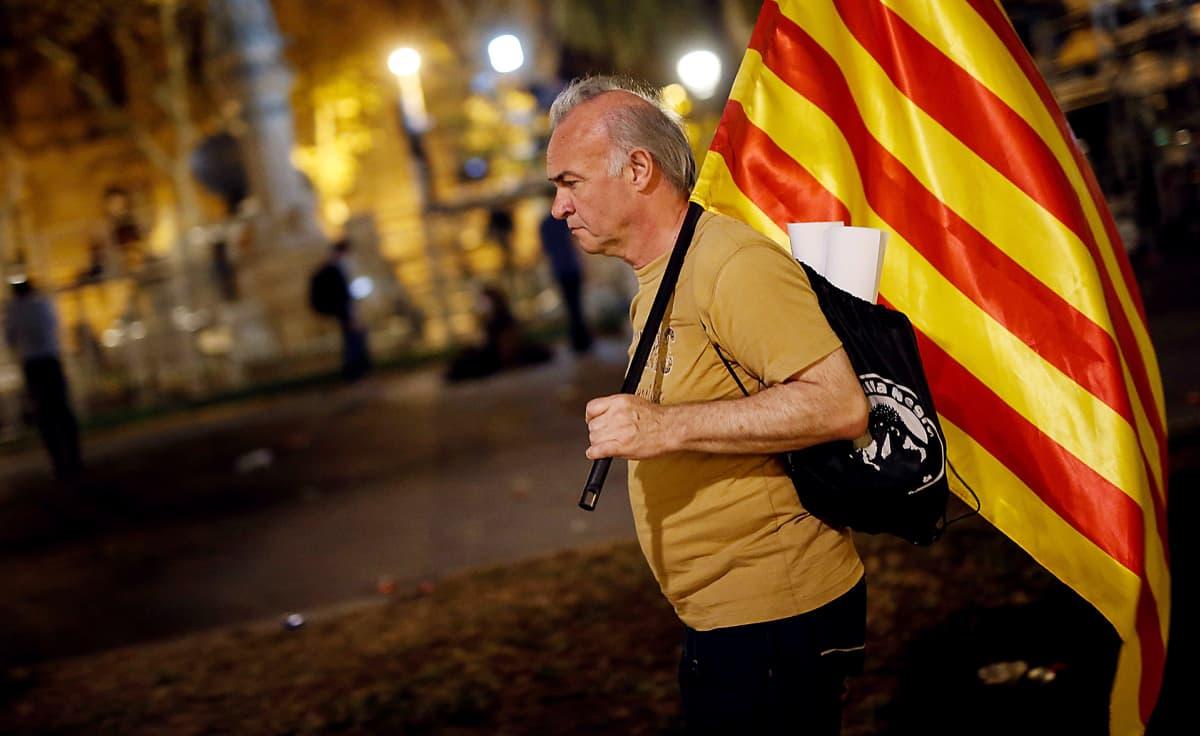 Mies kävelee Katalonian lipun kanssa