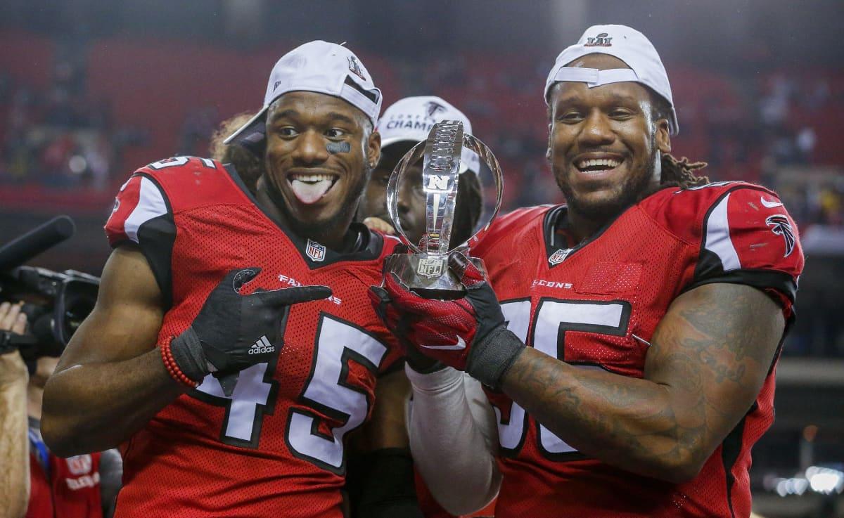 Atlanta Falconsin Deion Jones (vas.) ja Jonathan Babineaux juhlivat konferenssimestaruutta.