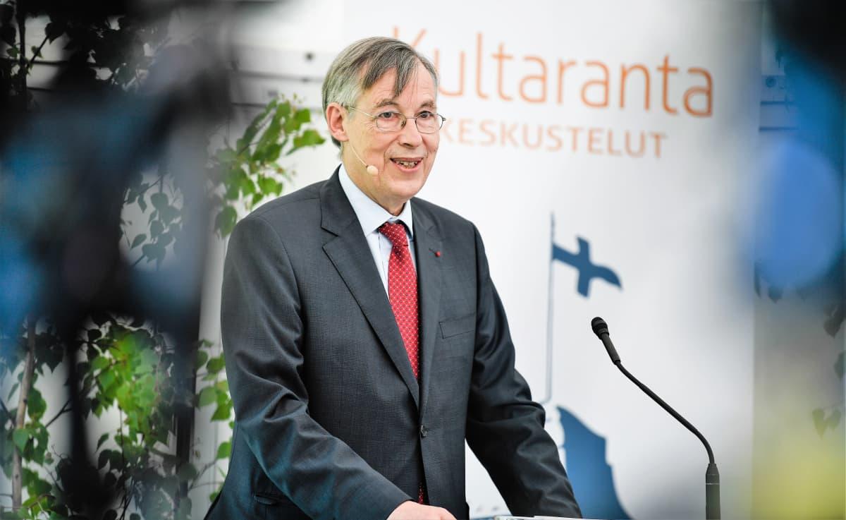 Franҫois Heisbourg puhuu mikrofoniin. Hänellä on yllään tummanharmaa puku, punainen kravatti. Taustakankaassa näkyy teksti Kultaranta-keskustelut ja Suomen lippu.