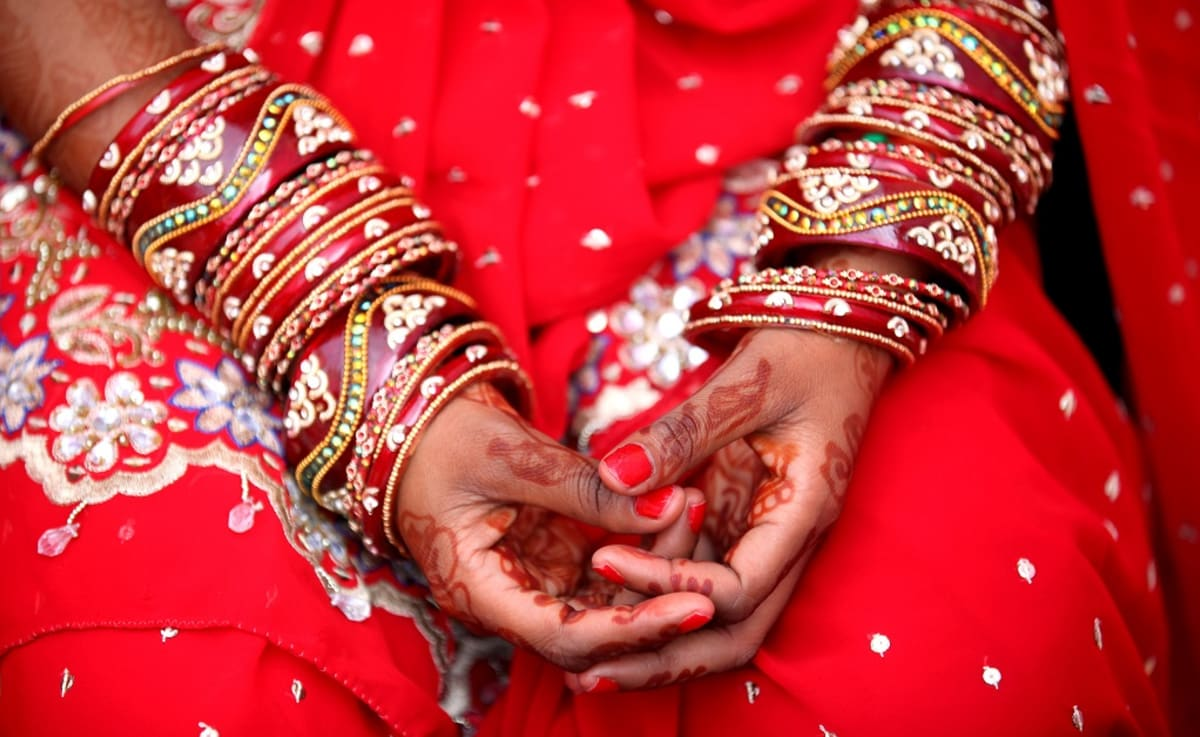 Lähikuva punapukuisen morsiamen käsistä. Käsivarsissa ja ranteissa kietää koristeellisia punaisia nahkanauhojan, ihoon on piirretty hennalla kuvioita.