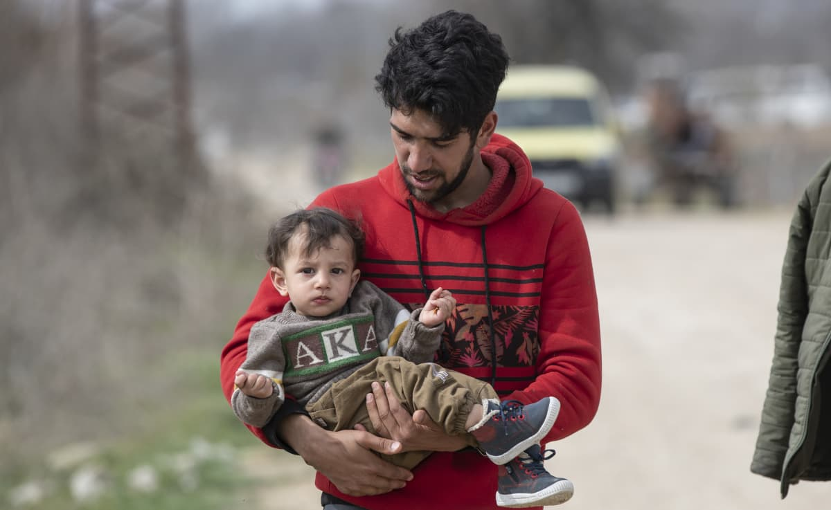 Mies kantoi poikaansa lähellä Kreikan raja-asemaa Edirnessä 9. maaliskuuta.