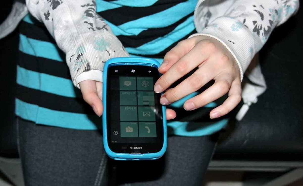 Lapsi käyttää kosketusnäyttöistä matkapuhelinta.