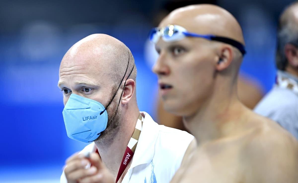 Kuvassa etualalla uimari Matti Mattsson uimalasit päässä, takana Mattssonin valmentaja Eetu Karvonen hengityssuoja kasvoilla.