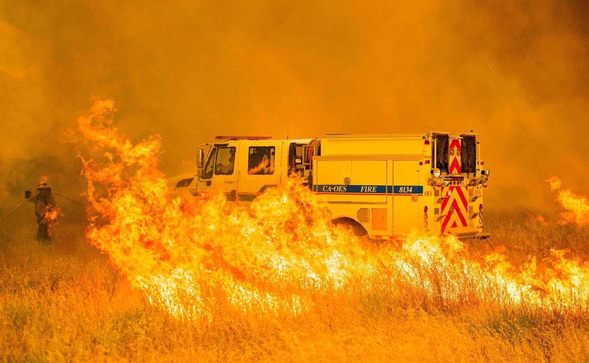 Tulipalo raivoaa Kaliforniassa. Paloauto on tiellä, jonka molemmin puolin nousee liekkejä.