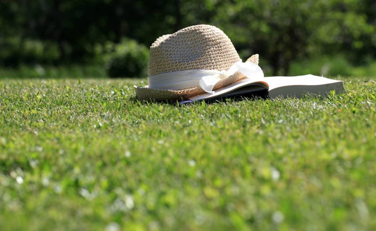 Hellehattu ja kirja nurmikolla.