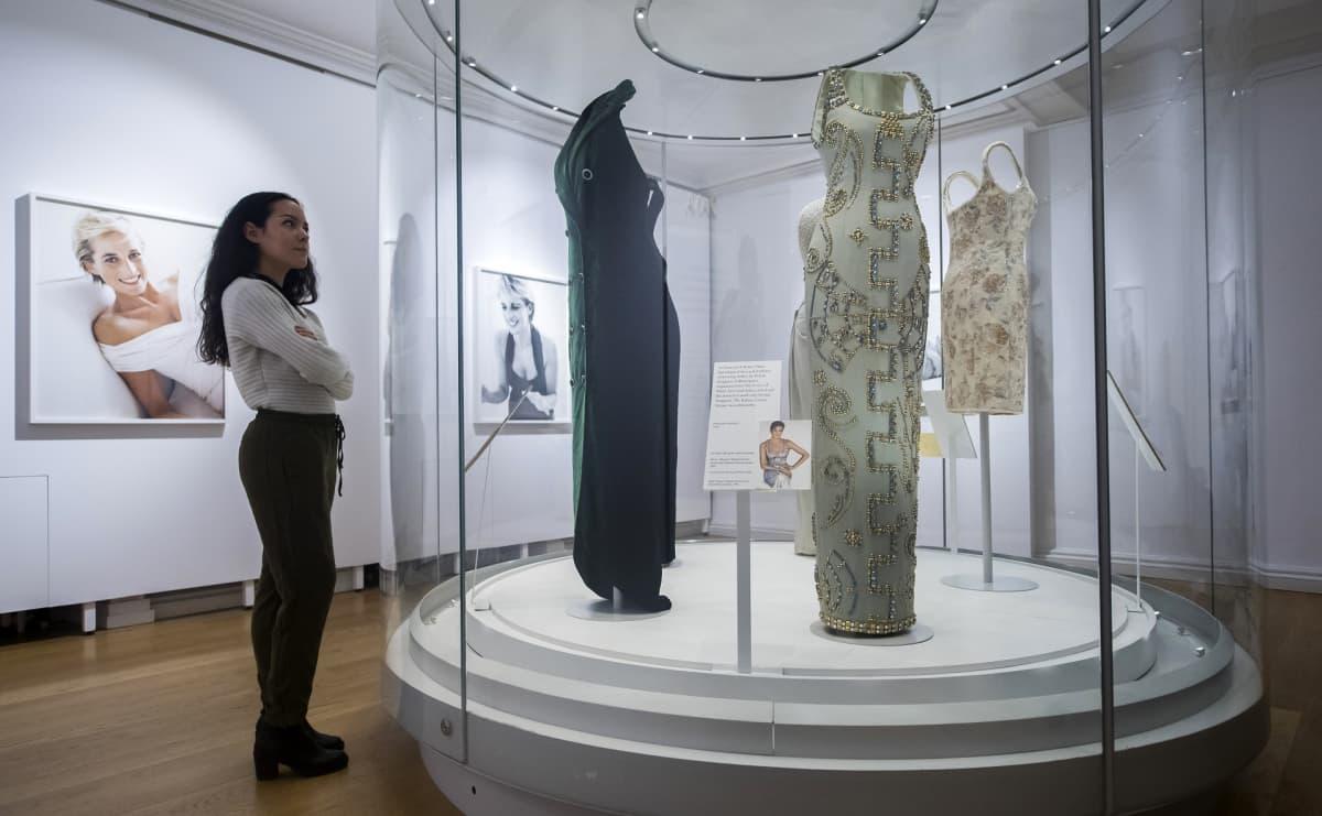 Mekkoja mallinukketorsojen päällä korokkeella, jota ympäröi läpinäkyvä seinä. Nainen seisoo vieressä. Takaseinällä on valokuvia prinsessa Dianasta.