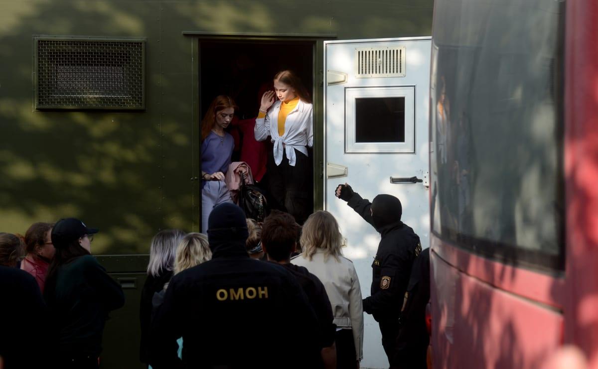 Poliisin autoon nostettuja nuoria naisia.