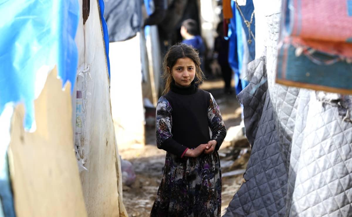 Noin kymmenvuotias vakavailmeinen tyttö pitkässä hameessa, kädet yhteen puristettuina seisoo sekalaisista kankaista pystytettyjen telttojen välissä.