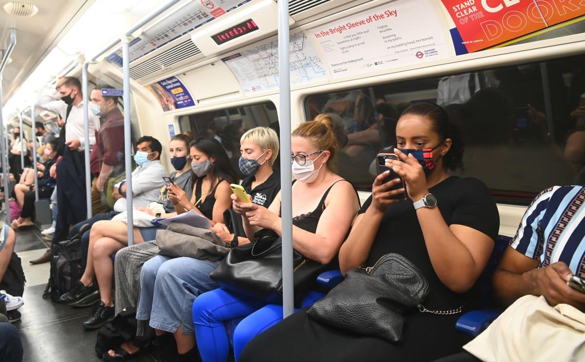 Ihmisiä ruuhkaisessa metrossa maskit kasvoilla.