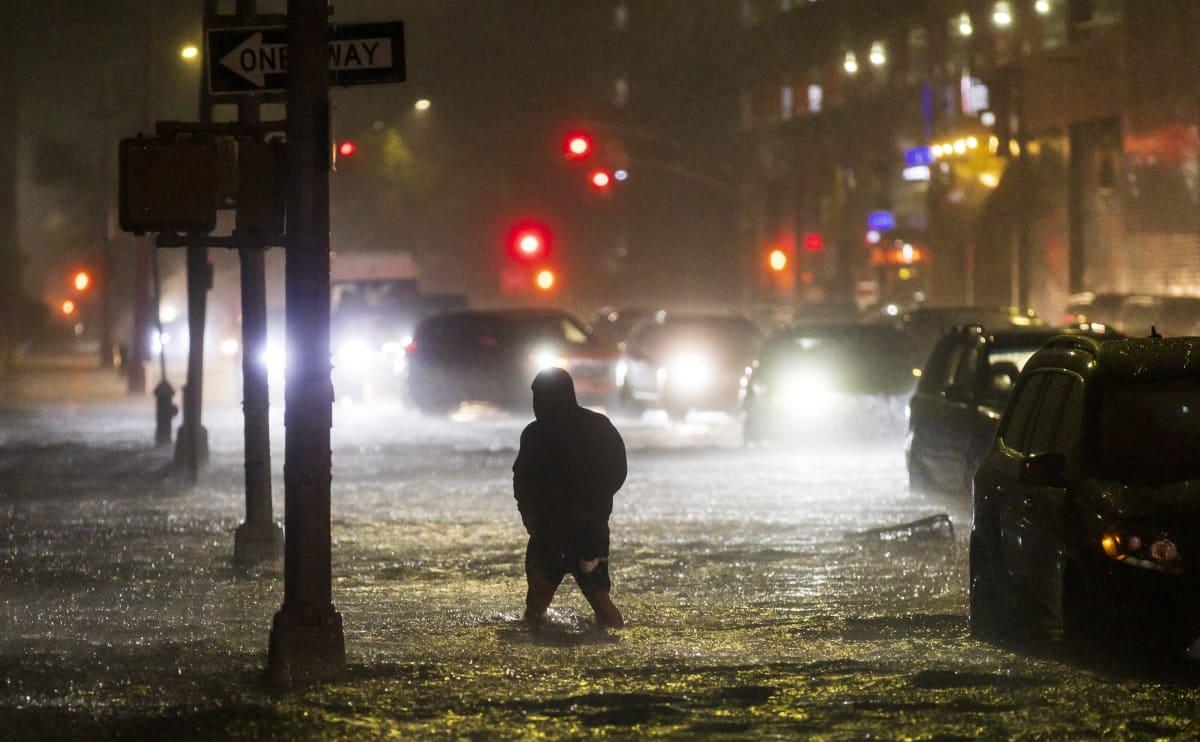 Henkilö  kahlaa tulvivalla kadulla autojen seassa