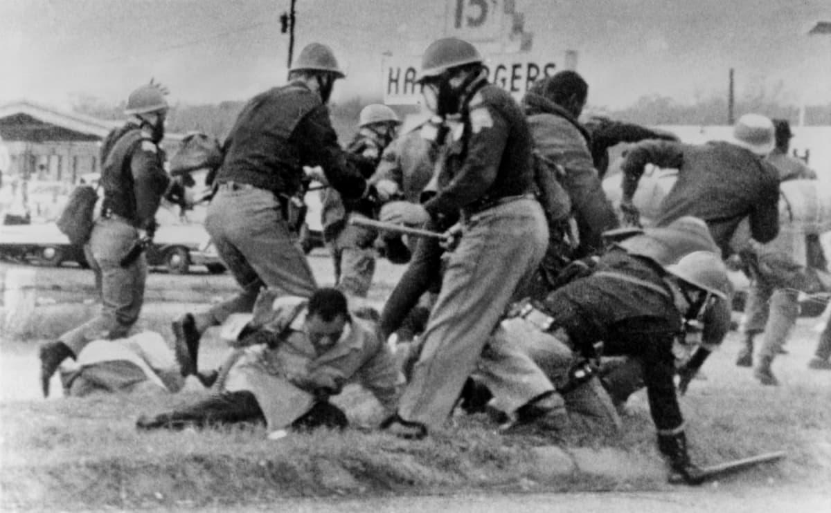 Mustavalkoisessa kuvassa valkoiset kypäräpäiset poliisit hakkaavat pampuilla maassa makaavia mustia.
