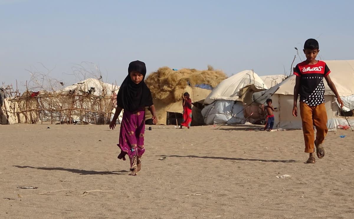 Lapsia kävelee teltan vieressä Hodeidan alueella Jemenissä.