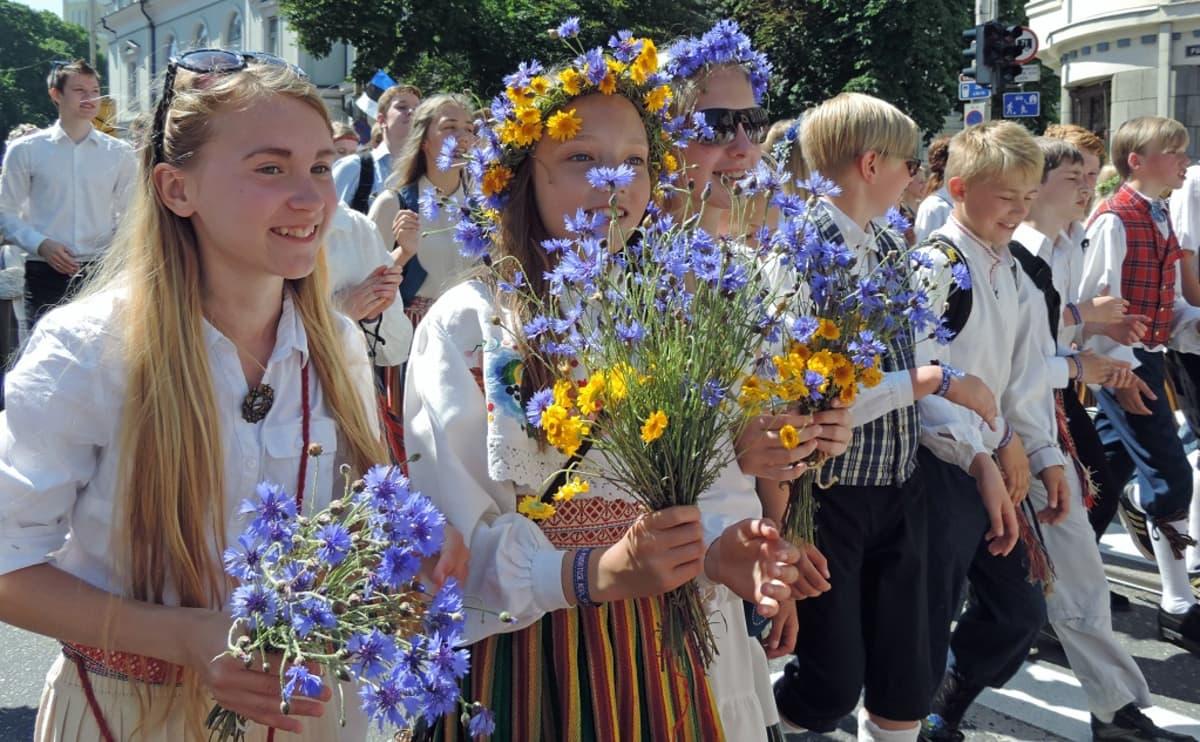 Hymyileviä kansallispukuisia tyttöjä, joilla on käsissään kukkia.