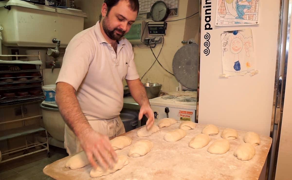 Sébastien Hayertz muotoilee taikinasta patonkeja jauhoisella pöydällä. Taustalla näkyy keittiöllaitteita.