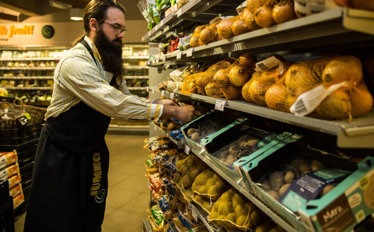 Myyjä asettelee perunoita hyllylle ruokakaupassa.