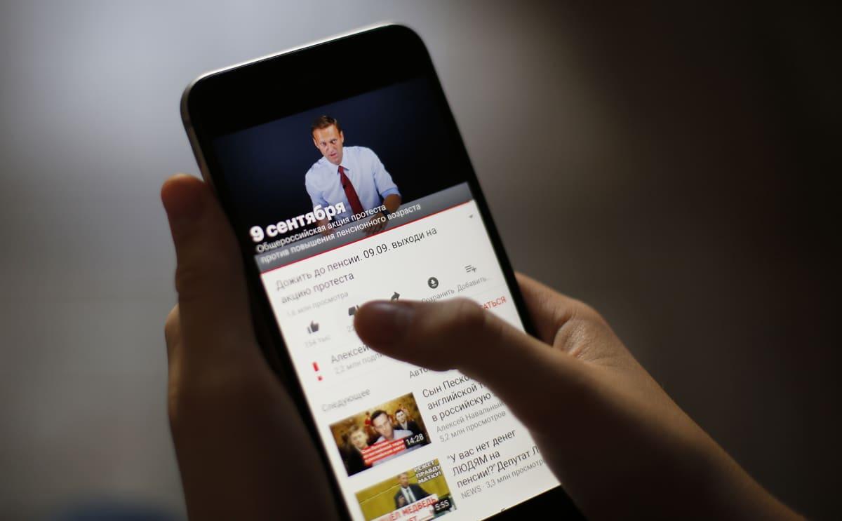 Venäläsnainen katselee YouTubesta oppositiojohtaja Aleksei Navalnyin videota, jossa hän kutsuu ihmisiä mielenosoituksiin aluevaalien aikaan syyskuussa 2018.
