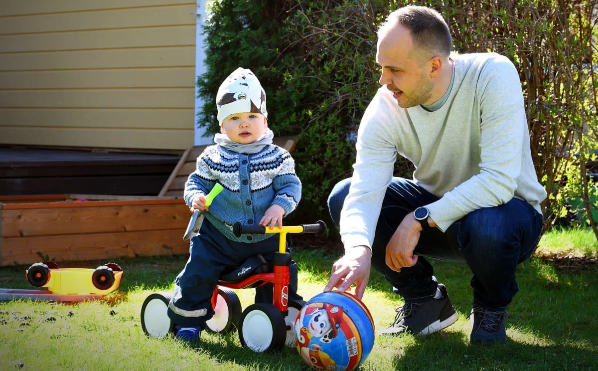 Martin Norrgård med sonen Aston på sin trehjuling hemma på gården
