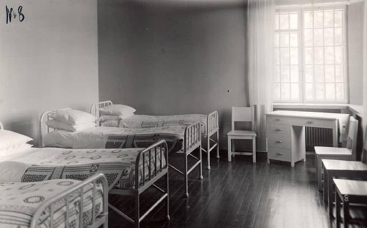 Neljä siististi pedattua sänkyä, lipasto ja tuoleja
