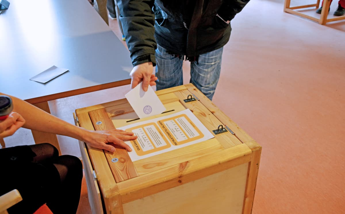 Kuvassa henkilö laittaa äänestyslipukkeen uurnaan.