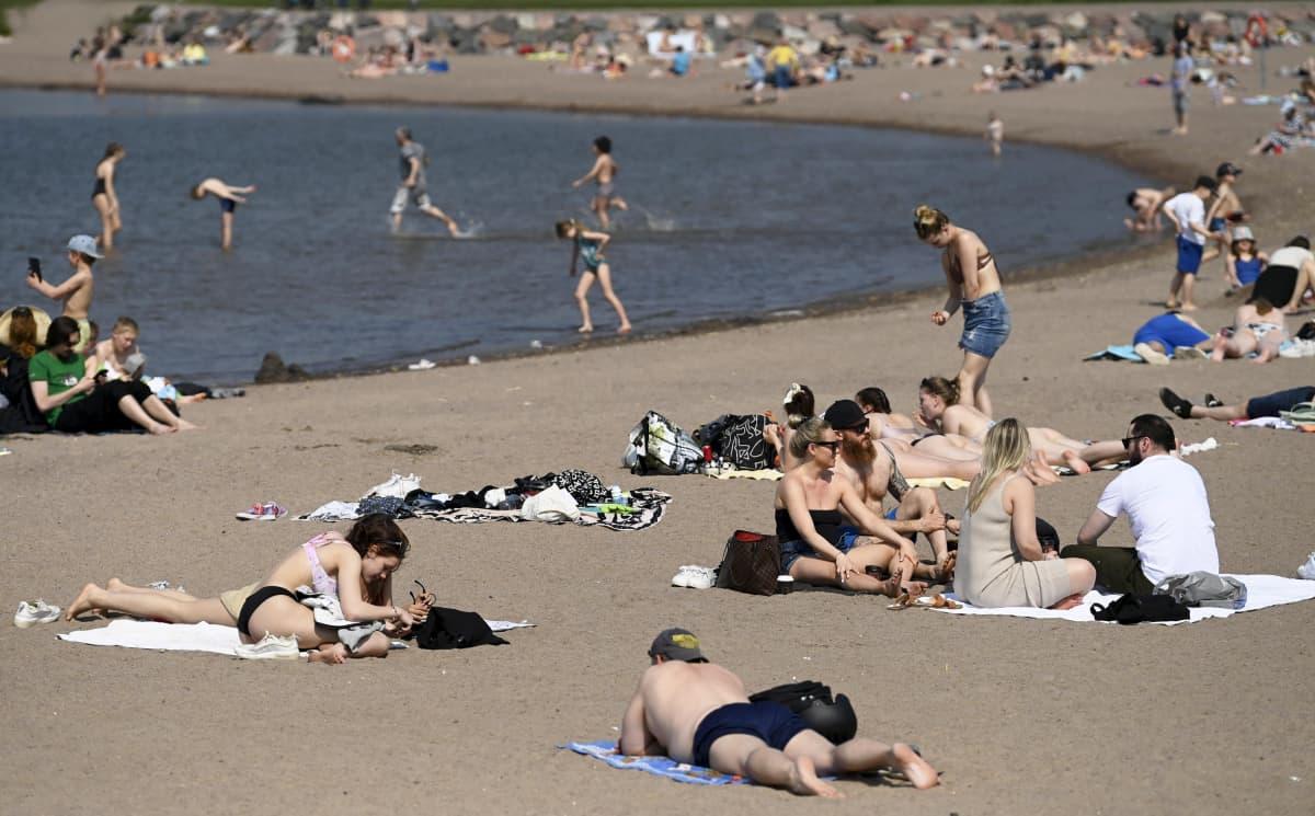 Auringonottajia Hietaniemen uimarannalla helatorstaina 13. toukokuuta 2021.