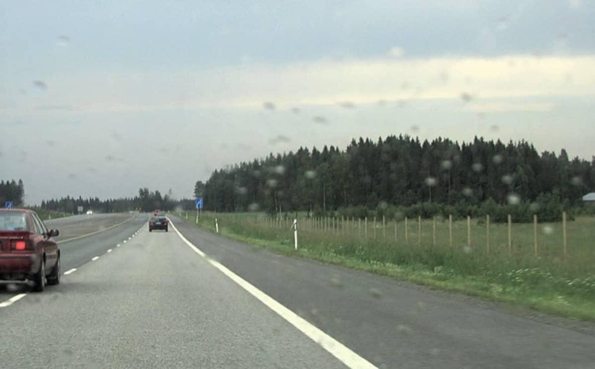 Punainen auto ajaa ohi ohituskaistalla. Kauempana edessä näkyy samaan suuntaan ajavia autoja.