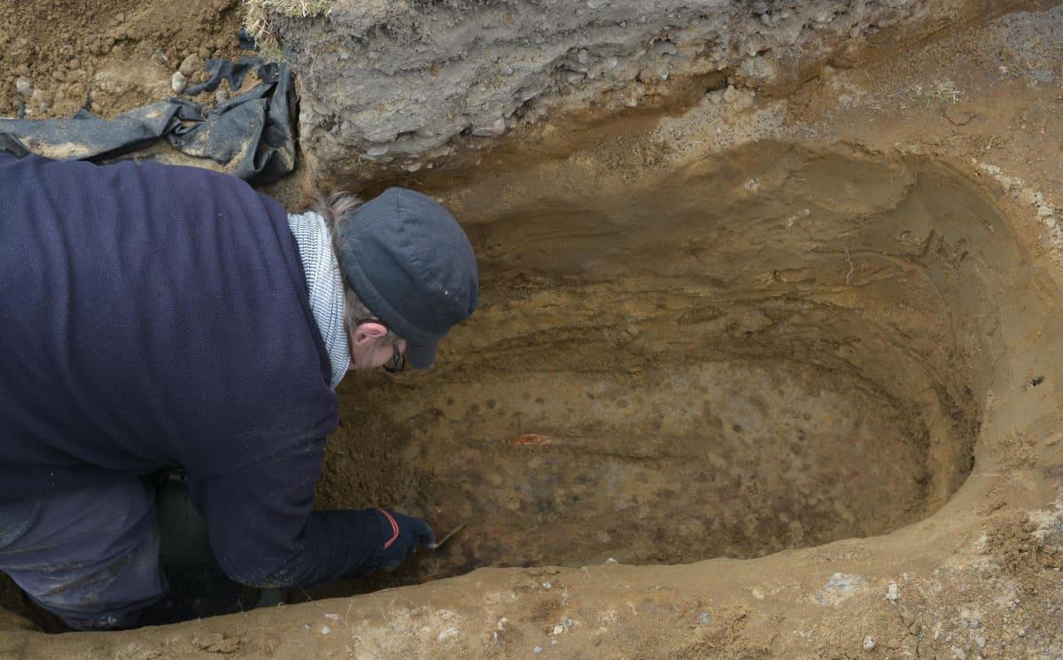 Anne-Mari Liira kaivaa haudan pohjalta esiin lapselle kuulunutta reisiluuta.