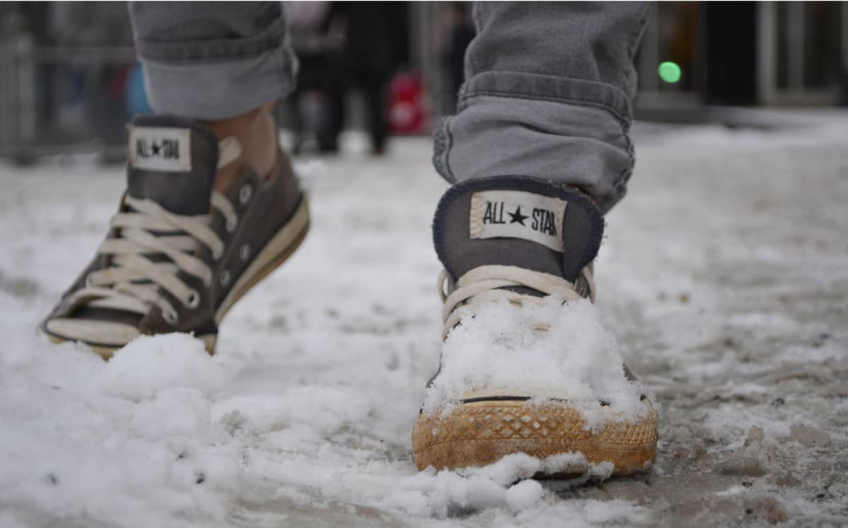 Teinillä jalassaan tennarit talvella.