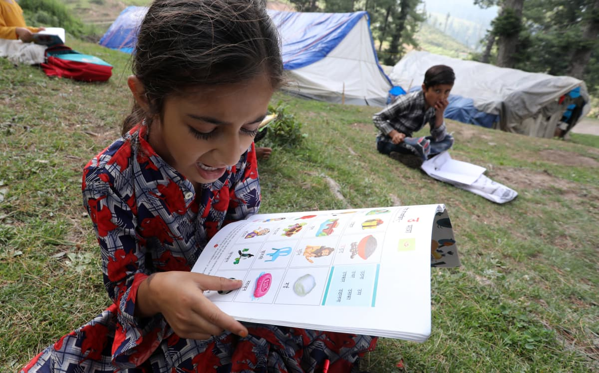 Koululaiset oppitunnilla ulkona Jammussa, Intiassa. Koronaviruksen takia kaikki koululaitokset on suljettu, ja opiskelu tapahtuu etäopetuksena.