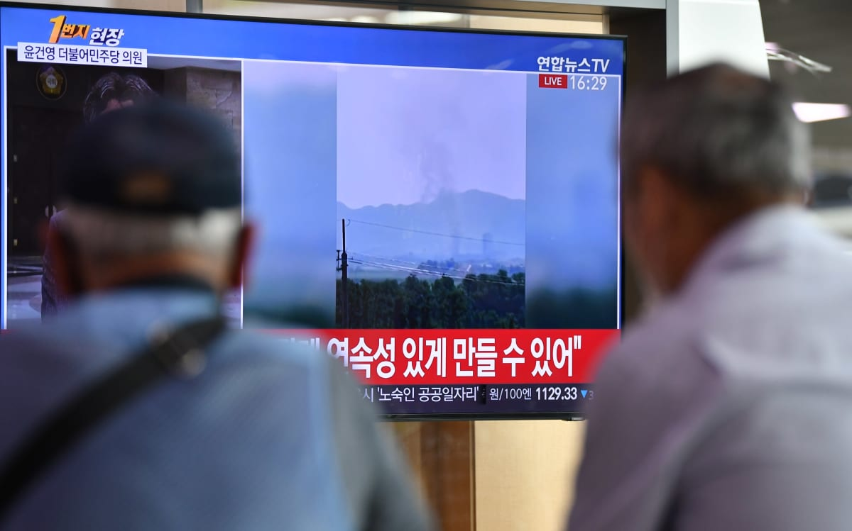 Ihmiset katsovat televisiota, jossa näytetään Koreoiden välisen yhteysviraston räjäytystä.