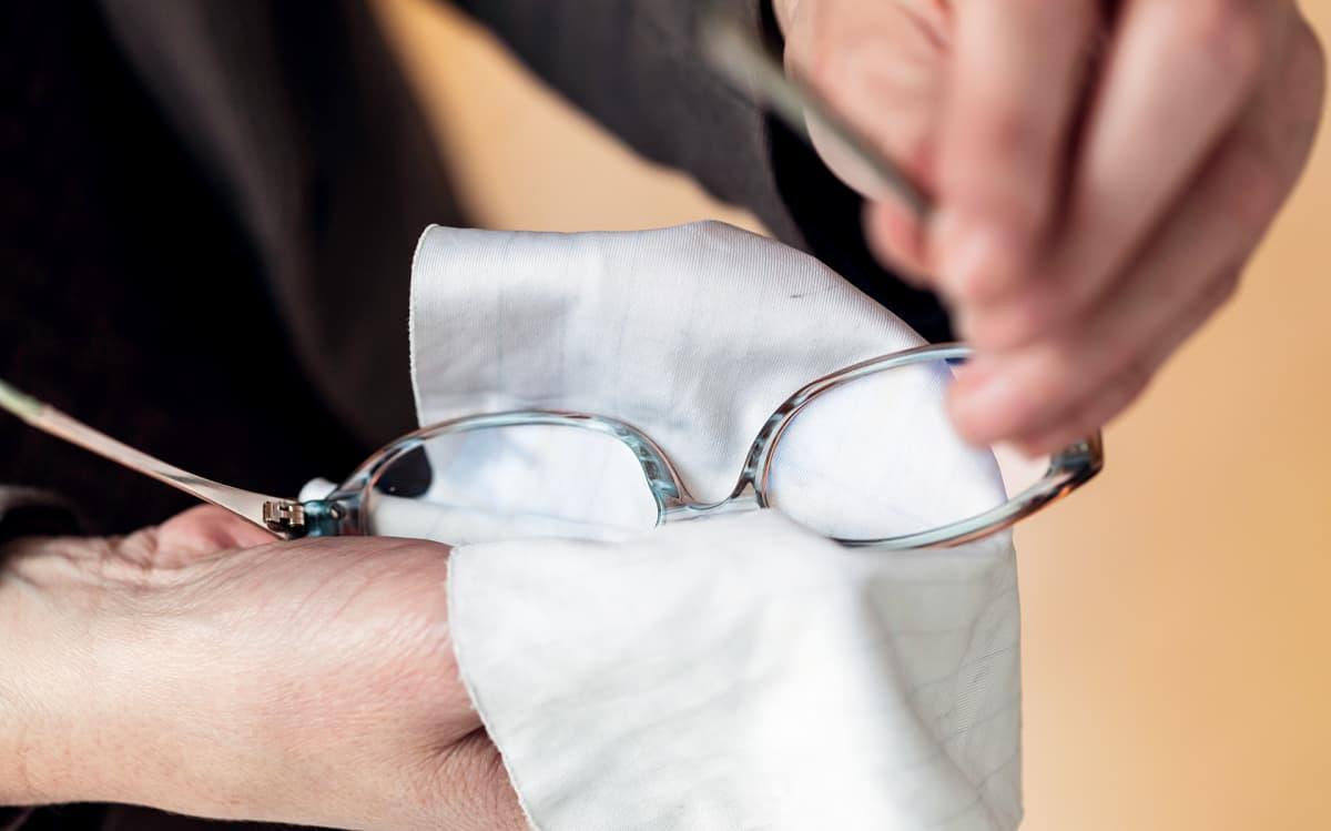 mies puhdistaa silmälaseja liinalla