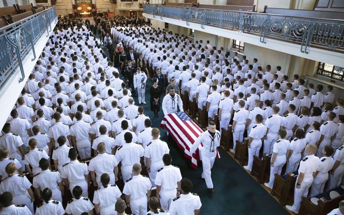Kuvassa arkkua kannetaan kirkon käytävää pitkin. Kappelissa paljon valkopukuisia laivastoakatemian opiskelijoita.