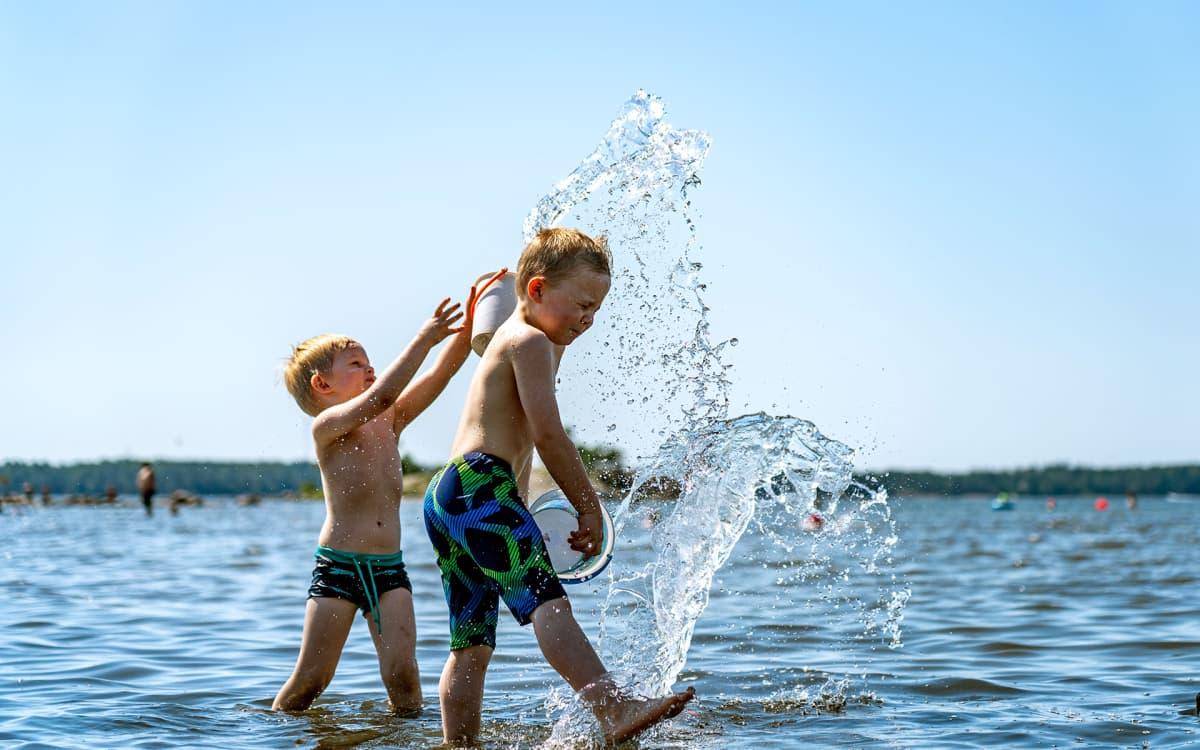 lapsi heittää vettä toisen lapsen päälle rannalla