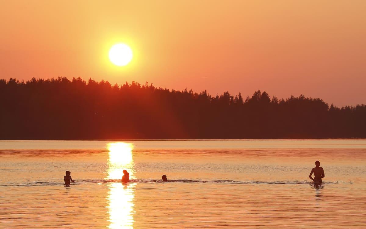 ihmisiä uimassa auringonlaskussa