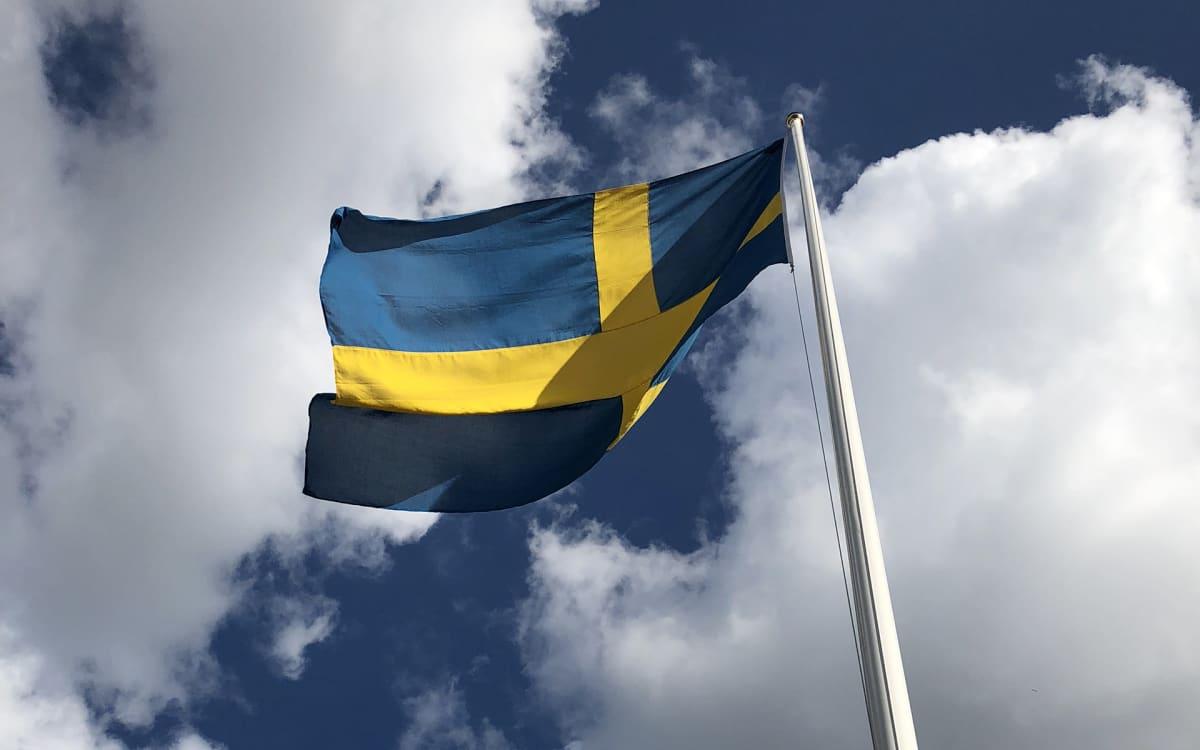 ruotsin lippu liehuu, valkoisia pilviä ja sinistä taivasta