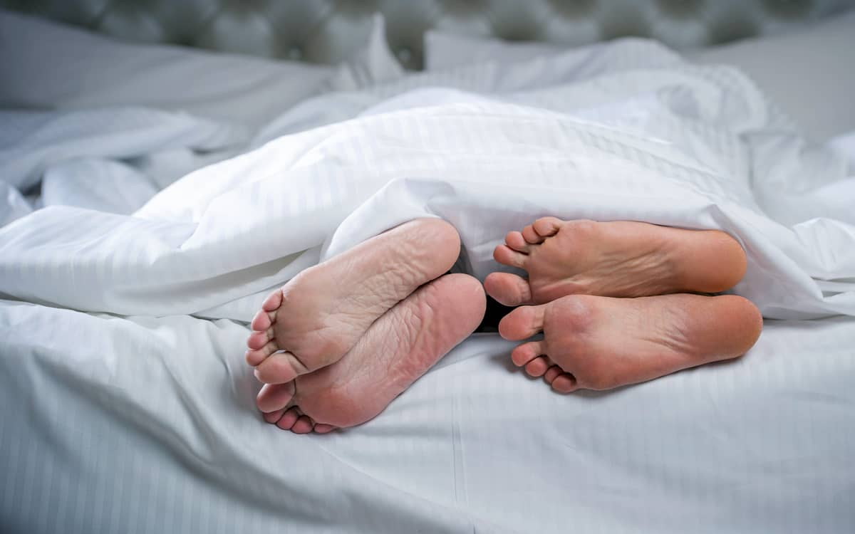 miehen ja naisen jalat pilkistävät peiton alta