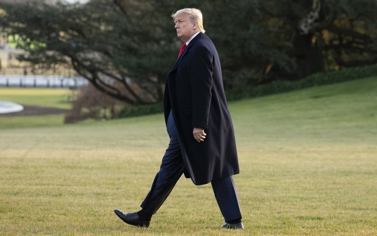Donald Trump kävelee valkoisen talon nurmella