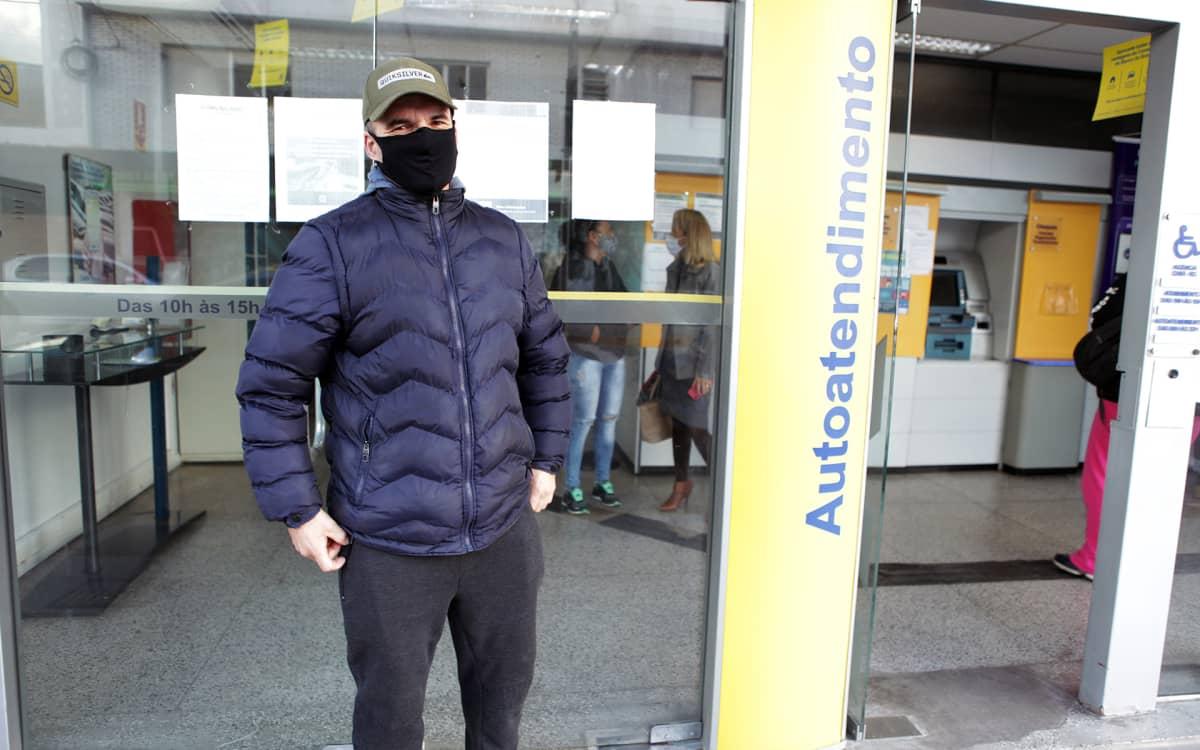 """Brasilialainen Andres Sousa odotti Chuíssa pankkivuoroaan. Hengityssuojaimen käyttö on kadulla pakollista. """"En ole kuullut, että kukaan olisi oikeasti saanut sakkoja"""", Sousa sanoo."""