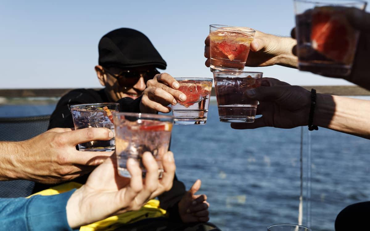 ihmiset kilistelevät juomiaan terassilla