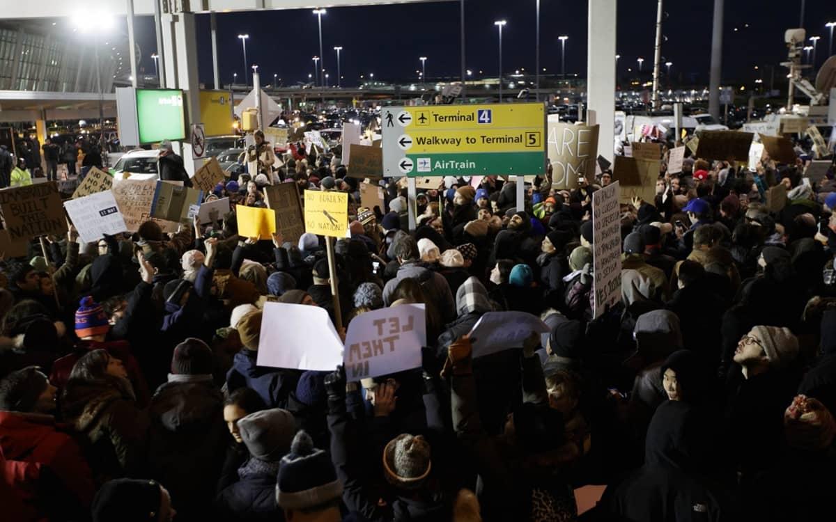 Ihmiset kantoivat kylttejä John F. Kennedyn lentokentällä mielenosoituksessa New Yorkissa 28. tammikuu 2017.