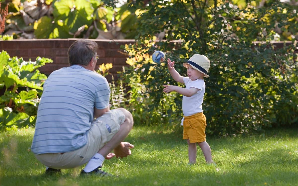 Ukki pelaa palloa lapsenlapsensa kanssa pihalla