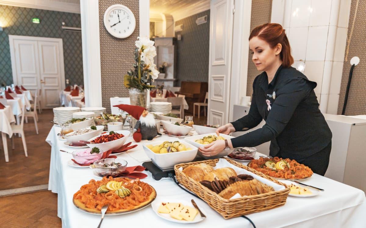 Ravintolapäällikkö Elina Pellonpää kattaa Wanhan Fredan joulupöytää Jyväskylässä.