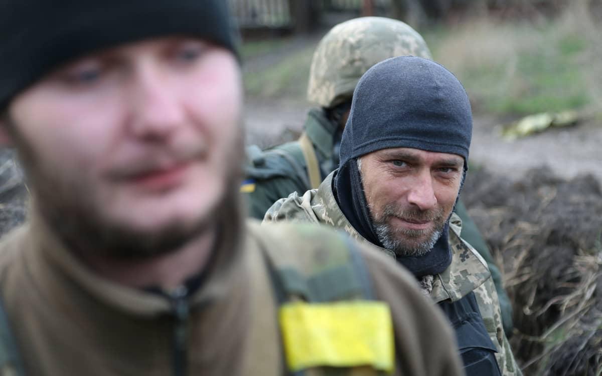 Ukrainan armeijan sotilas Artom taistelukavereineen miettii, miten hakea pois vihollistaistelijoiden ruumiit poteron läheisyydestä Avdijivkassa Itä-Ukrainassa.