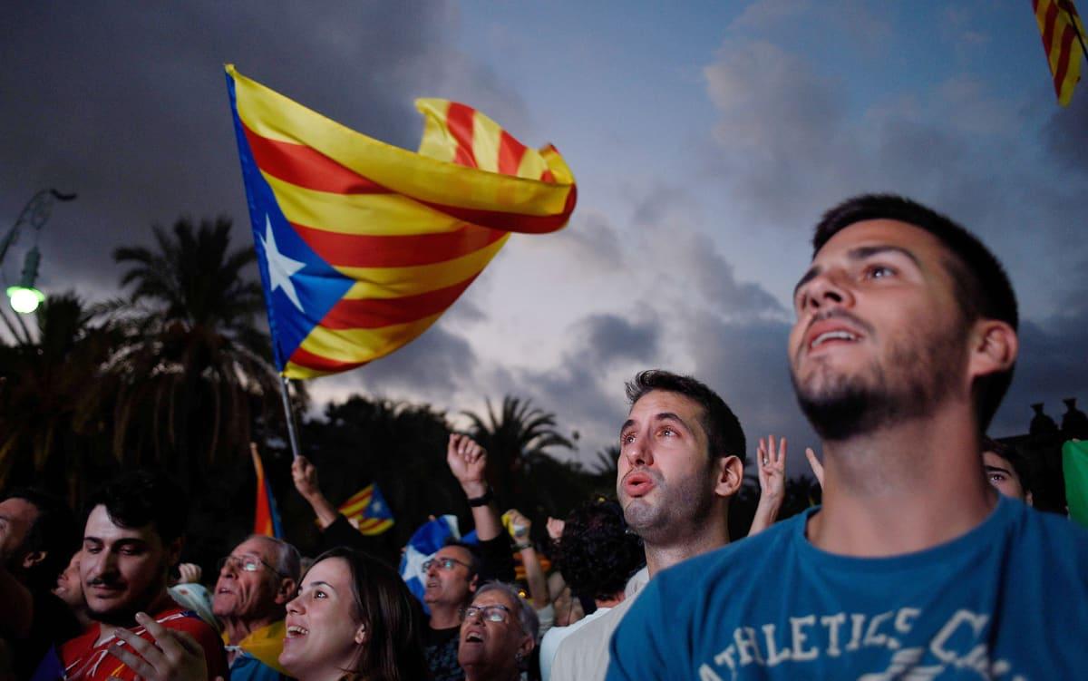 Katalonian itsenäisyyttä kannattavat ihmiset kuuntelivat Carles Puigdemontin puhetta televisiosta Barcelonassa 10. lokakuuta.