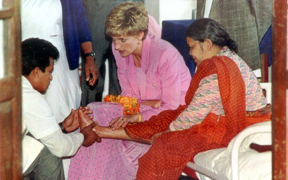 Diana koskettaa kädellään spitaalia sairastavan naisen jalkaa.